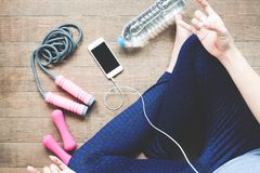 Fitness woman listening music on mobile device, Sport equipment, Bottle water on wood. Floor Royalty Free Stock Photos