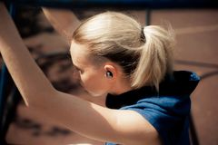 Fitness Woman Listening Music in Wireless Headphones, Athletic Fit Girl Relaxing After Training. Sport style Bluetooth earphones. Fitness Woman Listening Music Royalty Free Stock Photo