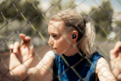 Fitness Woman Listening Music in Wireless Headphones, Doing Workout Exercises On Street. Sport style Bluetooth earphones. Fitness Woman Listening Music in stock image