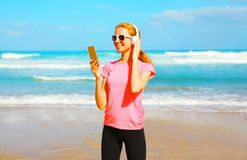 Fitness woman listens to music in a wireless headphones with smartphone Stock Photography