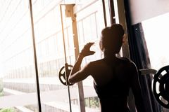 Fitness woman in loft gym drinking water After a good workout stock photography