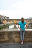 Fitness woman looking on ponte vecchio in florence, italy. rear Royalty Free Stock Photography