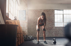 Fitness woman looking tired after intense workout. Shot of young woman in sportswear bending with her hands on knees at the gym. Fitness woman looking tired Royalty Free Stock Photo