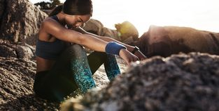 Woman looking tired after intense workout. Fitness woman looking tired after intense workout. Sportswoman sitting over rocks at the beach Stock Image