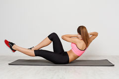 Fitness woman lying doing crunches stock images