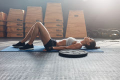 Fitness woman lying on her back after a gym workout. Side view shot of fitness woman resting on exercise mat with a heavy weight plate on floor. Female athlete Stock Photos