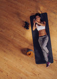 Fitness woman lying on mat using mobile phone Royalty Free Stock Image