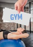 Fitness woman lying over exercise ball with hand holding text with placard Stock Photography