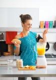 Fitness woman making pumpkin smoothie in kitchen Stock Photos