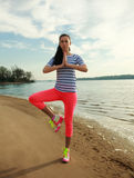 Fitness woman making yoga exercises on sand beach of river Royalty Free Stock Image