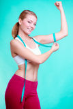 Fitness woman with measure tape measuring biceps Stock Photo