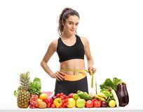 Fitness woman with a measuring tape behind a table with fruit an. D vegetables isolated on white background Stock Photos