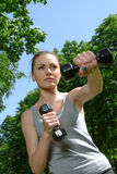 Fitness woman mimics a hit with light dumbbells Stock Photo