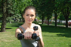 Fitness woman mimics a hit with light dumbbells Royalty Free Stock Images