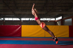 Fitness Woman Performing a Long Jump In Gym. Female Athlete Performing a Long Jump in Gym - One of the Best Jumping Exercise for Vitality Stock Image