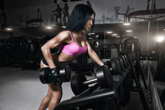 Fitness woman performs back exercisesin gym Stock Photo