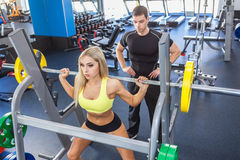 Fitness woman and personal trainer in gym Royalty Free Stock Image