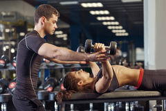 Fitness woman and personal trainer in gym stock images