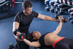 Fitness woman and personal trainer in gym. Man and women with barbell flexing muscles in gym. women and personal trainer in gym Royalty Free Stock Image