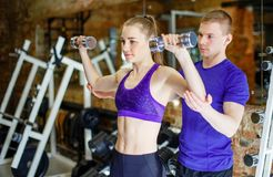 Fitness woman and personal trainer man with weight training equipment. Fitness women and personal trainer men with weight training equipment. The concept of Royalty Free Stock Photo