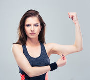 Fitness woman pinch a fat on her biceps. Over gray background Royalty Free Stock Photos
