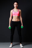 Fitness woman in pink top and black pants  doing dumbbells worko Royalty Free Stock Images