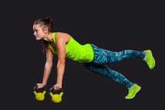 Fitness woman in plank position with kettlebells a Royalty Free Stock Photography