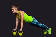 Fitness woman in plank position with kettlebells a Royalty Free Stock Photos