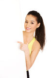 Fitness woman pointing on empty placard. Royalty Free Stock Image