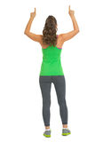 Fitness woman pointing up on copy space . rear view Royalty Free Stock Images