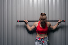 Fitness woman posing with barbell on shoulders. Portrait of young sporty woman wearing red top with barbell on shoulders. Sports girl posing against grey wall Royalty Free Stock Photography
