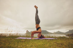 Fitness woman practicing headstand yoga outdoors Stock Images