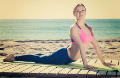 Fitness woman practicing set of stretching exercises. In nature Stock Image