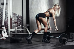 Fitness woman prepares for exercising with barbell in gym Stock Photography