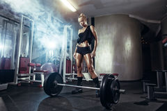 Fitness woman prepares for exercising with barbell in gym Stock Photos