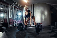 Fitness woman prepares for exercising with barbell in gym Royalty Free Stock Image