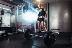 Fitness woman prepares for exercising with barbell in gym Royalty Free Stock Photography