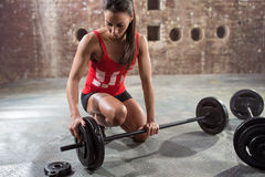 Fitness woman preparing to lift some heavy weights. Young fitness woman preparing to lift some heavy weights Royalty Free Stock Images