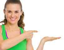 Fitness woman presenting something on empty palm Stock Photos