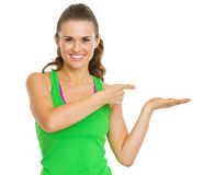 Fitness woman presenting something on empty palm Stock Images