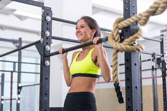 Fitness woman pull ups on horizontal bar in gym. Fitness woman pull ups on horizontal bar in gym Stock Images