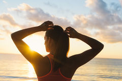 Fitness woman ready for summer sunrise beach workout. Back view of fitness woman getting ready for beach summer workout towards the sun. Sunrise morning training royalty free stock photos