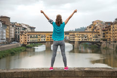 Fitness woman rejoicing in front of ponte vecchio in florence, i Stock Photos