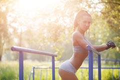 Fitness woman relax after workout exercises on bars outdoor Royalty Free Stock Photography