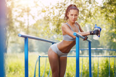 Fitness woman relax after workout exercises on parallel bars Royalty Free Stock Photography
