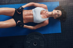 Fitness woman relaxing after exercise session. Overhead shot of woman relaxing after exercise session with a heavy weight plate on floor. Top view of young woman Stock Images