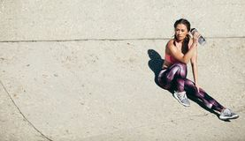 Fitness woman relaxing after workout session. Muscular female sitting outdoors and drinking water after exercising session. Fitness woman taking a break after Royalty Free Stock Photo