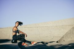 Fitness woman relaxing after workout. Fitness woman sitting on a exercise ball after workout. Female taking a rest after training session outdoors Stock Photo