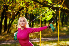 Fitness woman Resistance training in park. Portrait of beautiful smiling sportswoman doing resistance training in park Stock Image