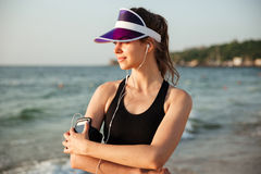 Fitness woman resting on beach listening to music with phone. Young fitness runner woman resting on beach listening to music with phone case sport armband strap Stock Image